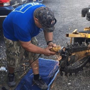 Thomas Zullo working on a trench digging machine for sprinkler irrigation installation